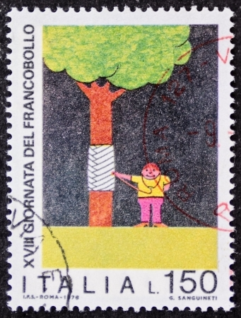 promotes: ITALY CIRCA 1976: a stamp printed in Italy promotes environmental protection depicting a boy auscultating by stethoscope a wounded tree. Italy, circa 1976