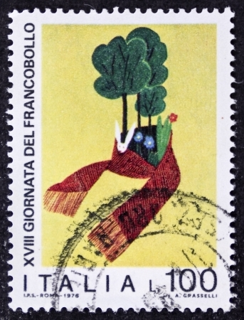 enveloping: ITALY CIRCA 1976: a stamp printed in Italy promotes environmental protection depicting a scarf  enveloping animals and plants. Italy, circa 1976
