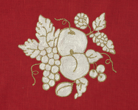 Embroidered fruits on red fabric photo