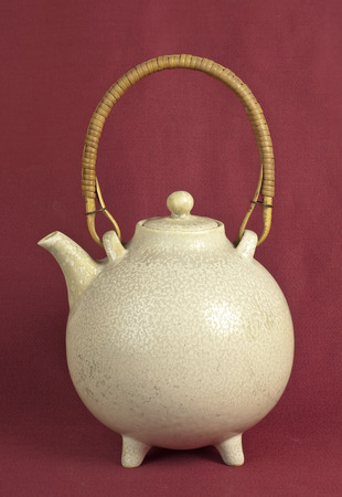 oxblood: Old ceramic teapot on oxblood red background