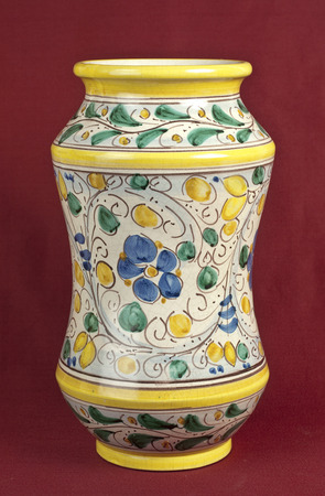 antique vase: Old decorated pharmacy jar on oxblood red background