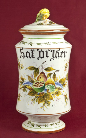 oxblood: Old decorated pharmacy jar on oxblood red background