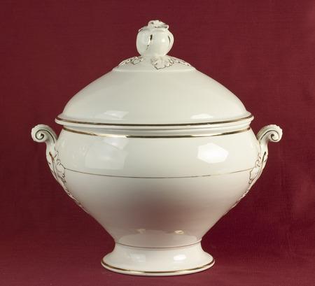 oxblood: Old porcelain tureen on oxblood red background