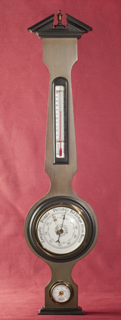 Banjo weather station on oxblood red background photo