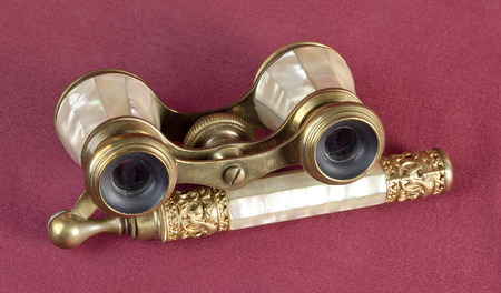 oxblood: Nacre and brass opera glasses on oxblood red background Stock Photo