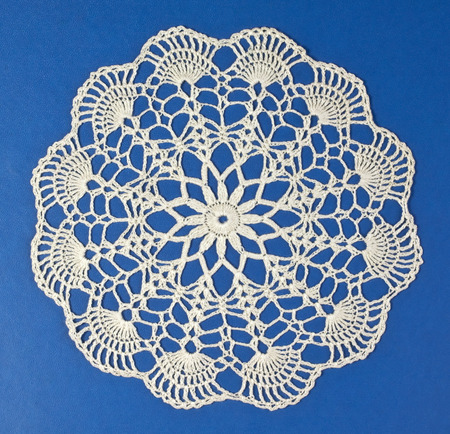 lace fabric: Handmade doily on blue background Stock Photo