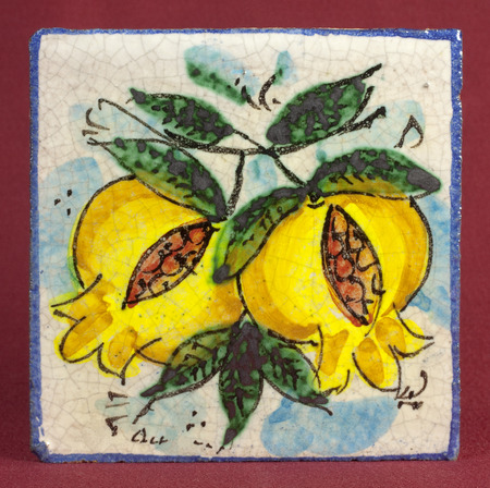 Old ceramic tile with pomegranate decoration Stock Photo