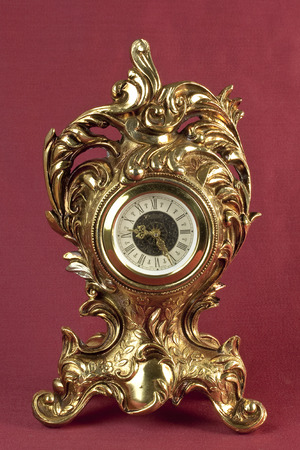 oxblood: Old bronze table clock on oxblood red background