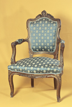 antique chair: Louis XV armchair on yellow ocher background Stock Photo