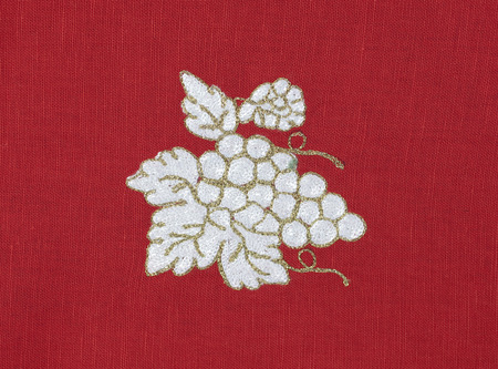 Embroidered grape on red fabric photo