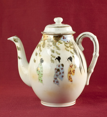 oxblood: Old chinese decorated teapot on oxblood red background