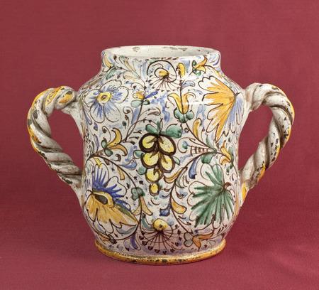 oxblood: Old decorated vase on oxblood background