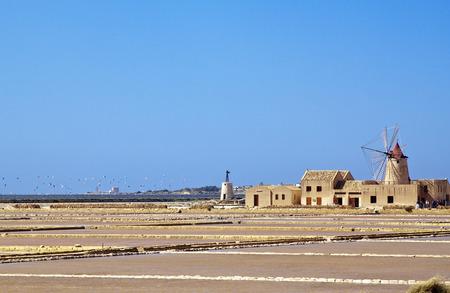 evaporacion: Salt evaporation ponds and windmill in Stagnone lagoon, Marsala, Sicily Foto de archivo
