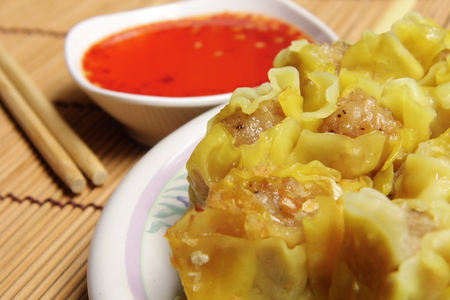 breakfast food: Chinese Pork dumpling with spicy sauce on bamboo mat