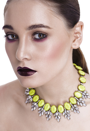 innuendo: White girl with dark make-up, with aubergine lips looking at the camera. Calle on the neck, shoulders open