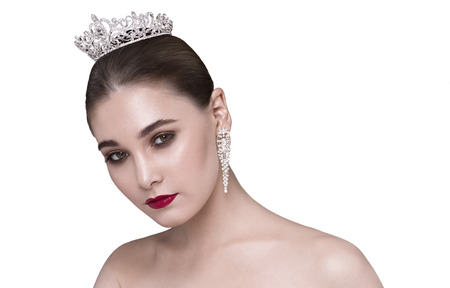 bare shoulders: Glamorous brunette with bare shoulders crown on his head looking at the camera head bowed Stock Photo