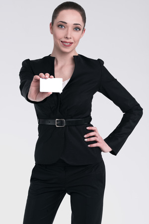 Woman standing in a pose, showing a white card