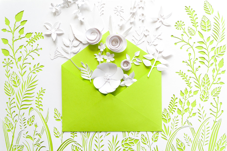 opened craft paper green envelope full of spring blossom sakura paper flowers on white background. top view. concept of love. happy valentines day. womens day. 8 of march. mothers day. Stock Photo