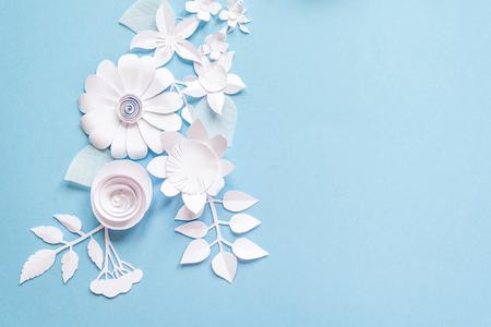 Frame met witte papieren bloemen op blauwe achtergrond Stockfoto