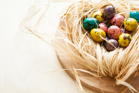 huevos de codorniz: Happy Easter. Colorful eggs in a wooden bowl  on wooden background
