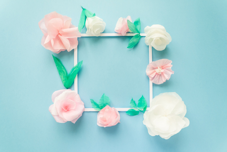square frame with color paper flowers on the blue background. Flat lay. Nature concept. Cut from paper. Place for your text.