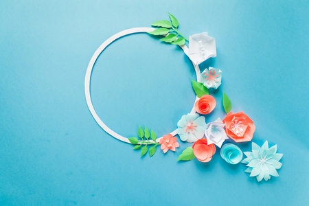 Round frame with color paper flowers on the blue background. Flat lay. Nature concept. Cut from paper. Place for your text.