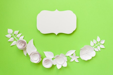 Vintage frame, semicircle frame with white paper flowers on the green background. Flat lay. Nature concept. Cut from paper. Place for your text.