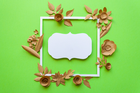 square frame with craft paper flowers on the green background. Flat lay. Nature concept. Cut from paper. Place for your text.