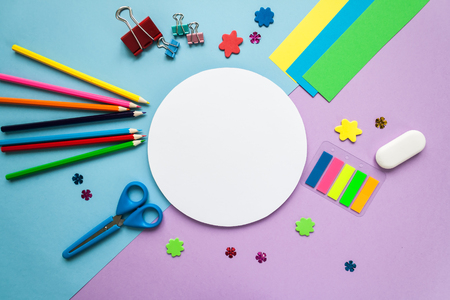 Back to school, round frame with stationery on blue and violet background. flat lay.