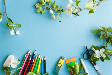 Good bay, school stationery and blosom apple brunch on blue background