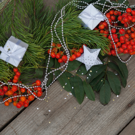 New year and Christmas background. Branches of the spruce and red ash with gifts and Christmas beads Stock Photo
