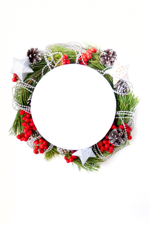 Merry Christmas and Happy new year. Round frame with branches firtree, gifts, pine cones and red berries Stock Photo