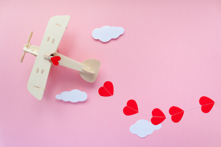 Happy Valentines day. Eco wooden childrens plane on a pink background with red heart, and garland in the shape of a heart white clouds, flags