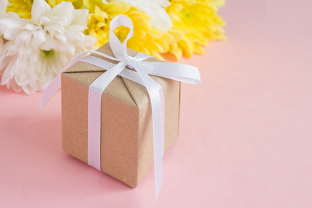 March 8 Women's Day card. Close-up gift and Bouquet of white and yellow chrysanthemums on a pale pink background
