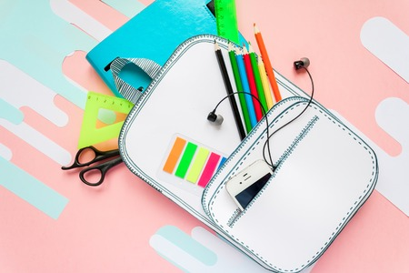 Creative school bag made of paper with school stationery on pink background. Trendy concept. Stockfoto
