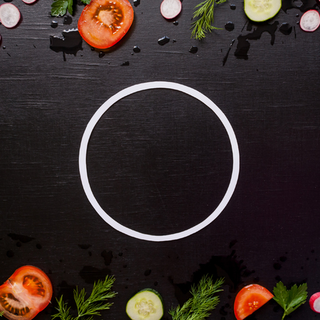border with sliced fresh vegetables on black background. Proper nutrition concept. Round frame 스톡 콘텐츠