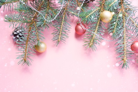 Merry Christmas and Happy New Year. Christmas Card Festive with green Fir Branches and Holiday Object on pale pink Background.