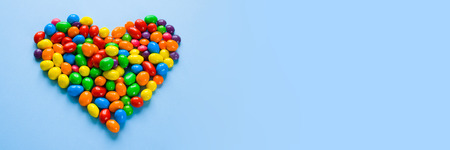 Colorful candies arranged as heart on blue background, long format for web Фото со стока