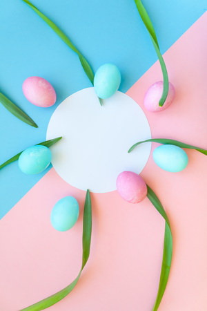 Round frame with beautiful white narcissus with colorful eggs on light blue and pink background. Spring and Easter holiday concept with copy space.