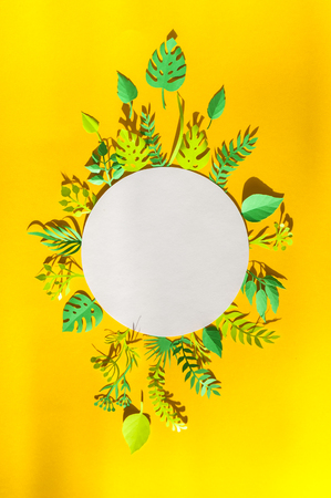 Round frame with reen tropical leaves cut from paper in the sun rays on a yellow background. Summer concept