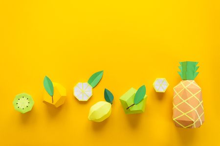 Fruit made of paper. Yellow background. Theres room for writing. Tropics. Flat lay. Pineapple, Apple, lemon, banana and kiwi. Yellow summer concept