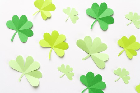 Happy St.Patricks Day, pattern of shamrock cut from paper on white background, text greeting card raster