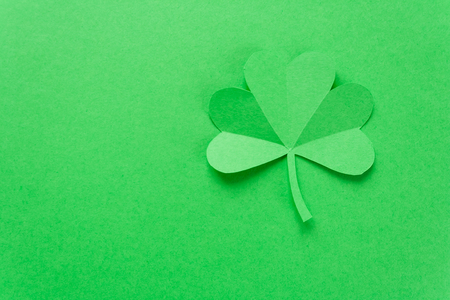 Happy St.Patrick's Day, shamrock cut from paper on green background, text greeting card raster