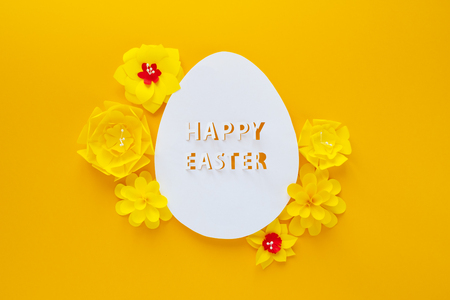 Happy easter. Easter egg made of white paper with yellow paper flowers on yellow background. Cut from paper. Stock Photo