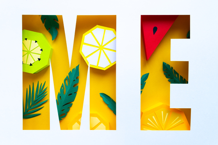 Yellow letter m, e cut out of paper with paper tropical fruit on white background. Form, counterform