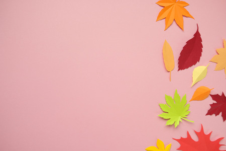 Leaves of paper fall red, orange, yellow leaf fall. Pink background. Handmade origami.