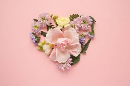 Heart made of different flowers on pink background. Flat lay. Love concept. Stock Photo