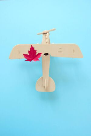 small toy plane with maple autumn leaf on blue background. Autumn concept