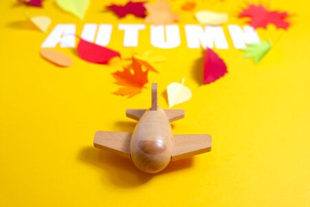 wooden toy airplane carries lettering autumn with leaves of paper fall red, orange, yellow leaf fall. Yellow background. Handmade origami.