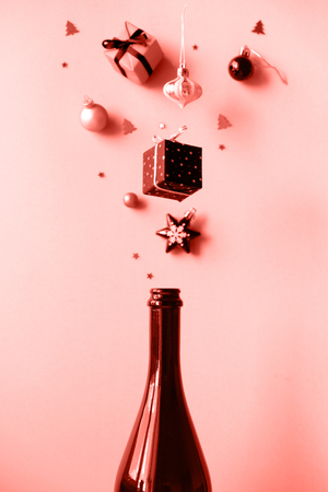 Champagne bottle with different christmas decoration on pink background.